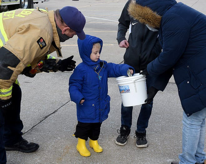 Nicholas Van Cleve, 4, makes a donation to the Food Bank of Central & Northeast Missouri with Columbia engineer firefighter Danny Spry, left, and food bank order clerk Shaun Meaders, right, on Wednesday during the One for One Holiday Food Drive at the Columbia Mall. Last year the food bank received $53,000 and food items during the one-day event. Donations can be made at sharefoodbringhope.org.
