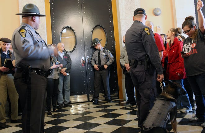 Members of the Ohio State Highway Patrol guard the doors amid protesters in April 2019 leading into the Ohio House chambers where members approved the so-called Heartbeat Bill, which banned virtually all abortions in Ohio once a fetal heartbeat could be detected. The law was put on hold pending a court challenge. The same chamber is expected to approve a bill Thursday that would ban medication abortions via tele-medicine.