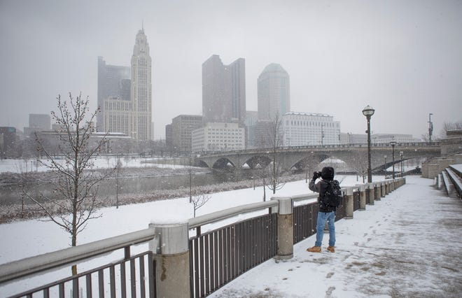 Jacob Hibbard, 19, of Stoutsville, Ohio takes a photo of the snow-covered skyline of downtown Columbus on Wednesday, Dec. 16, 2020. Winter weather passed through Central Ohio on Wednesday morning.