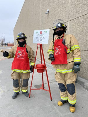 Firefighters Eli Sullivan and Garett Bengtson ring the bells for Salvation Army