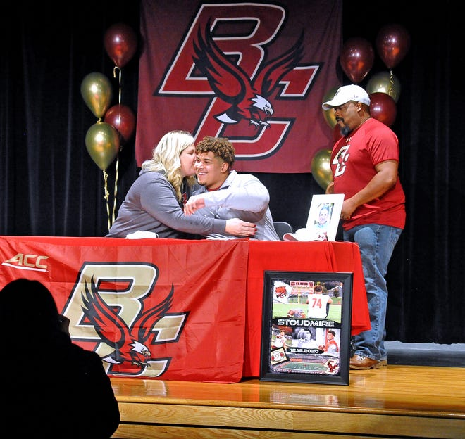 Norwayne's Owen Stoudmire gets a hug and a kiss from his mom, Melissa, after signing his National Letter of Intent to attend Boston College on a football scholarship. His dad, Kevin, looks on.