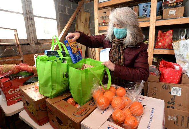 Heather Caspar, executive director of the Sisters of St. Joseph Neighborhood Network, works Wednesday in the facility's food pantry. The organization received an $80,000 federal CARES Act grant to support its food delivery efforts.