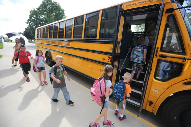 In this file photo students from North Hill Elementary School board school buses at the end of the school day, in Burlington, Iowa.