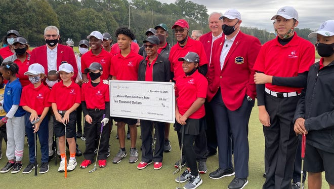 Justine Redding (center, black jacket) accepts a check for $10,000 from The Players Championship for the Moore-Myers Children's Fund, an area charity that supports participation in golf. The presentation came at the First Tee of North Florida at the Brentwood Golf Club.