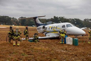 Jacksonville firefighters work on a fuel leak after a jet skidded off the Craig airport tunway