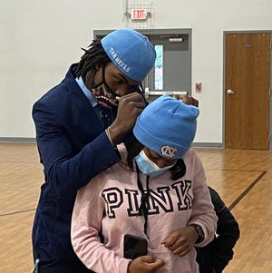 Hunter Huss' Dontavius Nash signs an autograph during a ceremony commemorating him signing with the University of North Carolina.