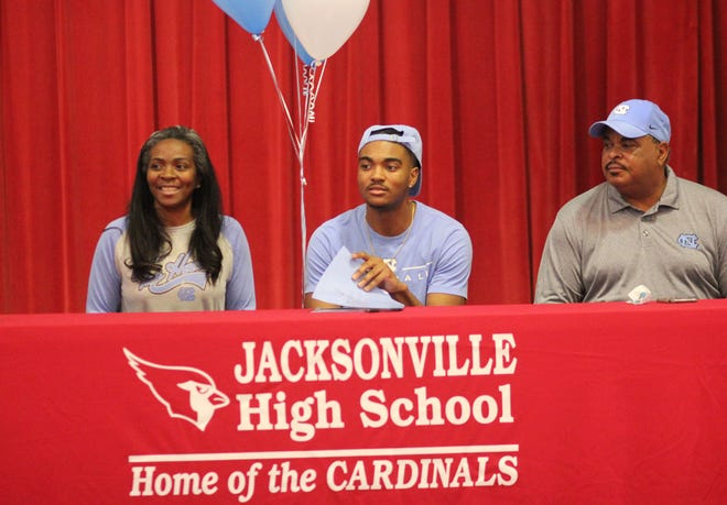 Jacksonville senior Tymir Brown, center, is joined by his mother, Tamika, and his father, Malton, as he signed to play football for North Carolina on Wednesday. [Chris Miller / The Daily News]