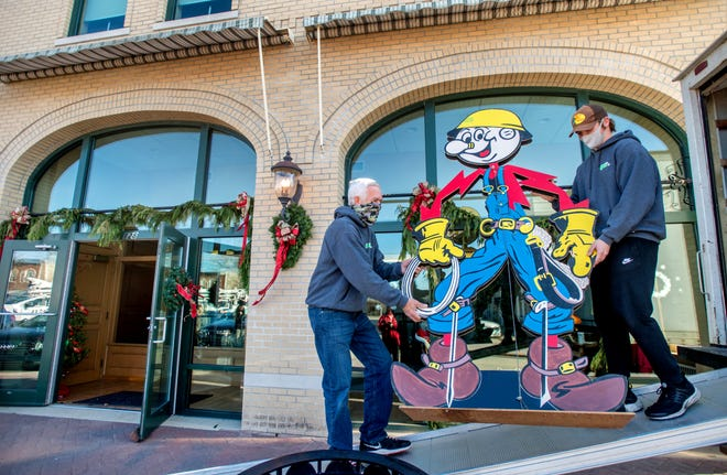 "Gary Folkerts, left, and Garrett Peterson of Alpha to Omega Movers, Inc. out of Eureka carry a big ""Reddy Kilowatt"" figure into the new headquarters of the Washington Historical Society on the second floor of the Danforth Building at 128 Washington Square in Washington. The front of the Danforth Building was restored in 2009 to duplicate its original 1897 appearance."