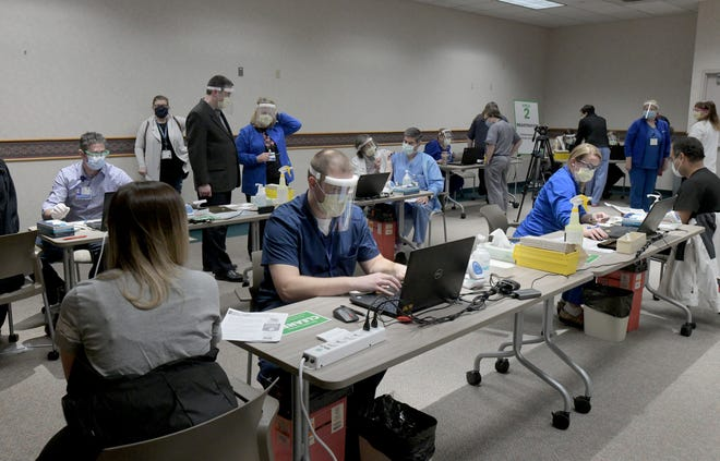 Four vaccination stations were set up in the Morron Room at UnityPoint Health in Peoria, where COVID-19 vaccinations began around 4 p.m. Wednesday.