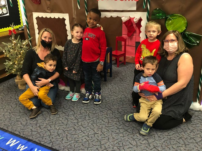 Joelle Grimsley and Melissa Bysura pose with some of their Lil' Bulldogs preschool students in front of the classroom's gingerbread house.