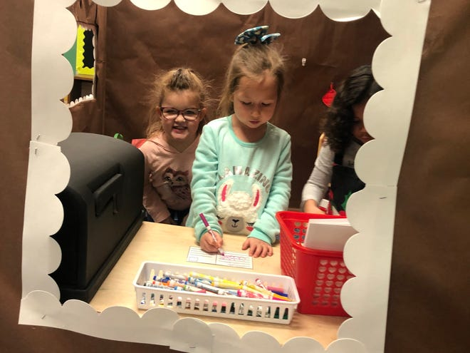Students in the Lil' Bulldogs preschool program work on holiday cards for family members while in the classroom's gingerbread house.