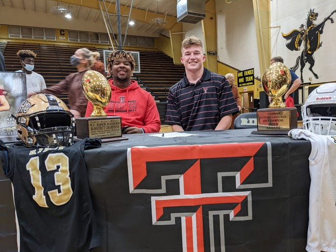 "Wichita Falls Rider defensive lineman E'Maurion ""Dooda"" Banks, left, and tight end Jed Castles sign with Texas Tech on Wednesday, the first day of college football's December national signing period."