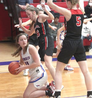 After grabbing a loose ball Tuesday, Moberly High School senior Claire Billington is surrounded by Hannibal's Ellie Locke and Jade Thomas (#5) as she looks to distribute the ball to a teammate. Billington and the Lady Spartans defeated Hannibal 49-25.