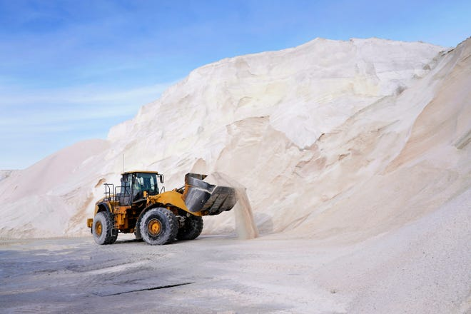A front loader works at a large pile of road salt, Wednesday, Dec. 16, 2020, in Chelsea, Mass., as preparation continues for a storm that is expected to dump a foot or more of snow throughout the Northeast. [AP Photo/Elise Amendola]