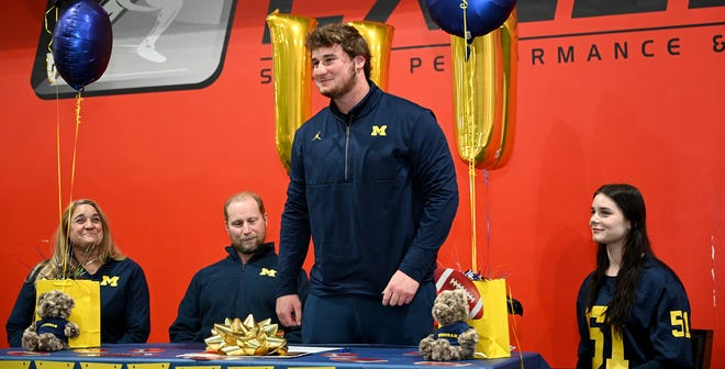Greg Crippen, of Northborough, stands to speak before signing his National Letter of Intent to play football at the University of Michigan during a brief signing ceremony at Exceed Sports Performance & Fitness in Westborough on Wednesday, Dec. 16, 2020. Looking on are his parents, Susanne and Tom Crippen, and sister, Karoline.