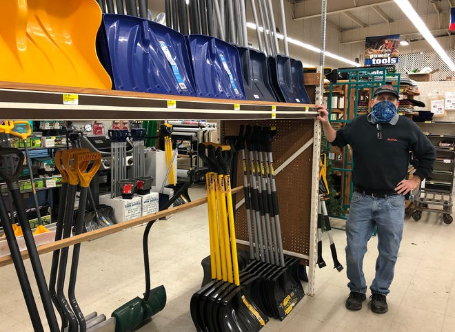 Employee Scott Baumgartner of the True Value location in Newport stands next to the store's stock of snow shovels on Wednesday.
