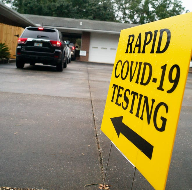 Signs direct drivers to the entrance of a drive-through COVID-19 rapid testing location in Florida. The facility, run by ProHealth, administers a 15-minute-result test.