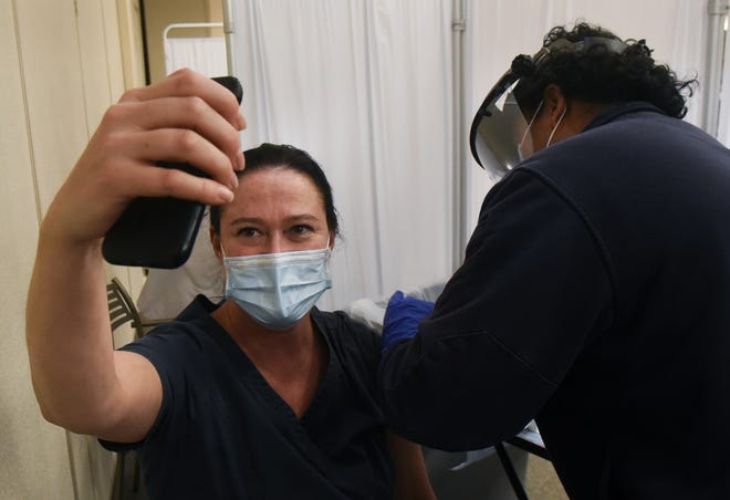 Exeter Hospital lab assistant Kristen Zimmerman takes a selfie as she received her first COVID-19 vaccine dose Wednesday, Dec. 16, 2020, along with other hospital staff members, who were among the first to receive it. Laurie Miller, an Exeter Emergency Room paramedic, administers the vaccine. New Hampshire has now announced its rollout plan for more vaccinations.