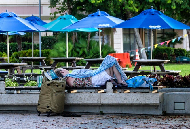 A woman sleeps by the Great Lawn and Lake Pavilion in downtown West Palm Beach. [LANNIS WATERS/palmbeachpost.com]