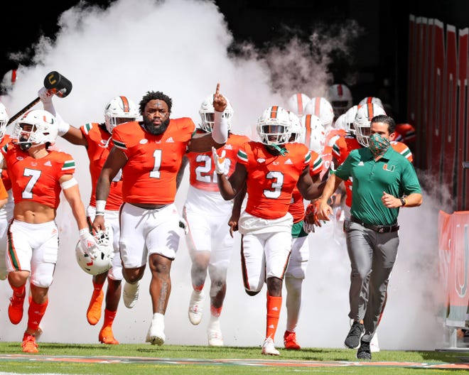 Miami coach Manny Diaz, shown leading his team onto the field this season against Pittsburgh, is convincing the top local players to stay home.