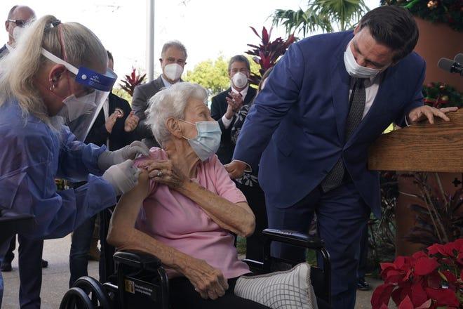 Florida Gov. Ron DeSantis asks Vera Leip, 88, how she feels after nurse Christine Philips, left, administered the Pfizer vaccine last December during a visit at John Knox Village in Pompano Beach. (AP Photo/Marta Lavandier)