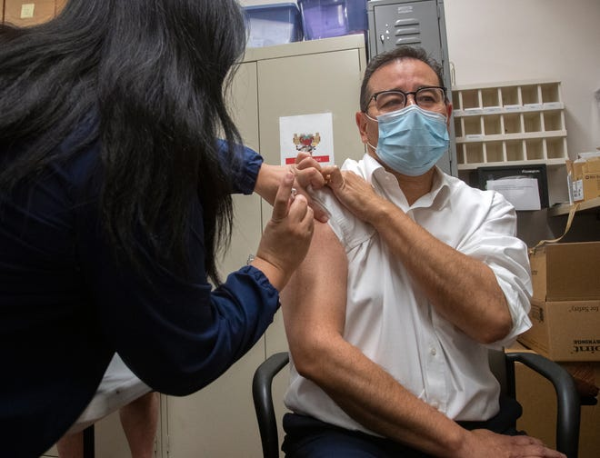 Dr. Michael Herrera, D.O., left, receives a shot of the Pfizer BioNTech COVID-19 vaccine at St. Joseph's Medical Center in Stockton.