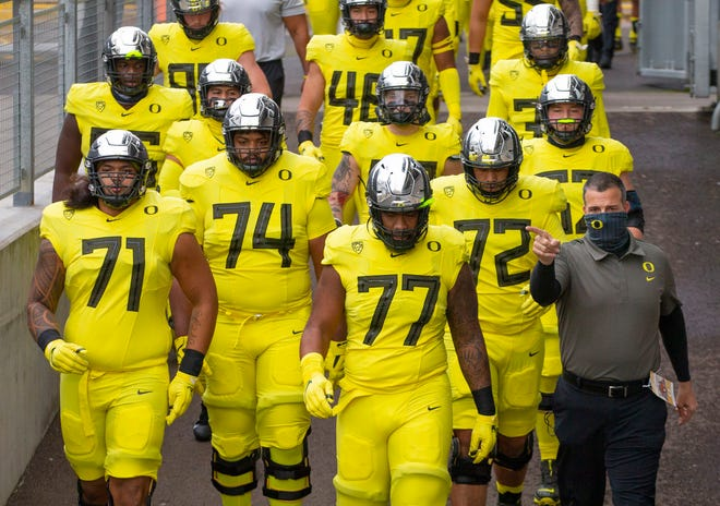 Oregon coach Mario Cristobal, right, leads his team onto the field at Reser Stadium in Corvallis before this past season's game against Oregon State.