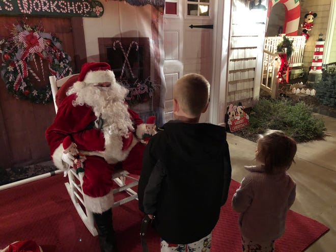 Carson Judy, 6, and his sister Maisyn, 3, meet with Santa Claus on at the Katie Land display in Plain Township.