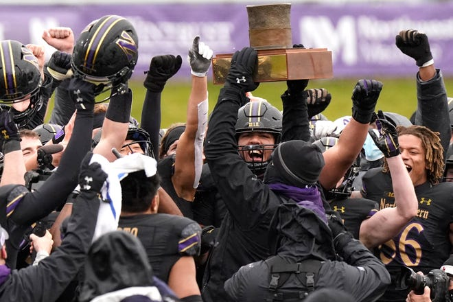 Northwestern football head coach Pat Fitzgerald celebrates with players as he holds the Land of Lincoln Trophy after Northwestern defeated Illinois 28-10 Saturday in Evanston.