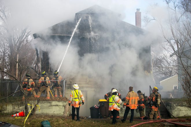 Firefighters work to control a blaze at a home at 1621 Green St. on Wednesday in Rockford.