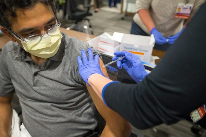 Mercyhealth Registered Nurse Michelle Pressney administers a COVID-19 vaccination to Dr. Venkata Dontaraju at Javon Bea Hospital-Riverside in Rockford on Wednesday, the first day the shots were administered in the city.