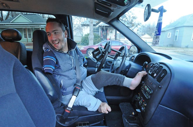 David Powell, of Salina, checks the back seat before getting ready to drive his Dodge Grand Caravan that was modified to help him be able to drive. Powell can now legally drive on the road after a 2 1/2-year-long process of overcoming several obstacles. Powell was born with leg and arm deformities that resulted in him having no hands and malformed legs, and he has been wanting to be able to drive his entire life.