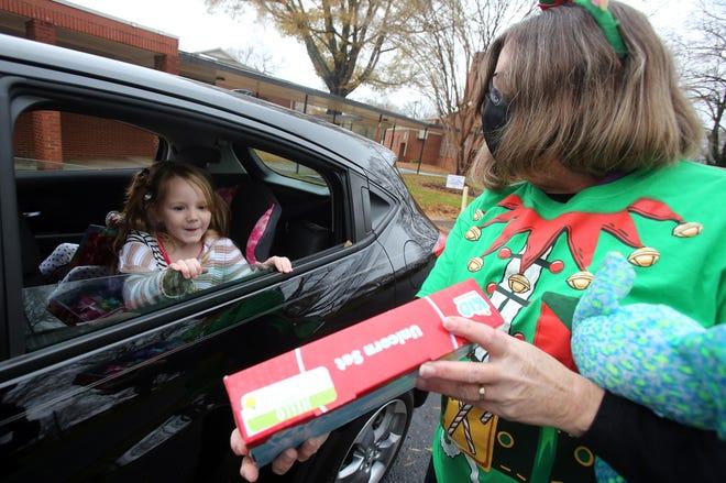 Ellie Tesseneer, 5, sees her gift held by head start teacher Mary Gloege at a giveaway held at Graham Elementary School on Wednesday.