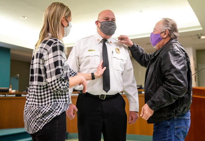 Brandon Blough is pinned as the new Springfield fire chief by his father, Bill Blough, a former Springfield firefighter, and his wife, Tamara Blough, after being confirmed by the Springfield City Council, on Tuesday in the City Council Chambers in Springfield. [Justin L. Fowler/The State Journal-Register]