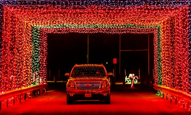 """With its lights turned off to take in the lights, a pickup truck is illuminated for a short moment as the synchronized lights turn on in unison as it makes its way through the lighted tunnel during the Chatham Friends of the Parks' drive-through holiday light display """"Light up the Park"""" at Chatham Community Park on Dec. 21, 2017, in Chatham. [Justin L. Fowler/The State Journal-Register]"""