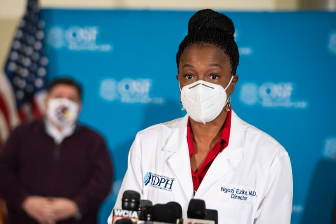 Gov. J.B. Pritzker looks on as Dr. Ngozi Ezike, director of the Illinois Department of Public Health, speaks to reporters after a nurse administered Illinois' first five Pfizer-BioNTech COVID-19 vaccinations outside of Chicago at OSF Saint Francis Medical Center in downstate Peoria, Ill., Tuesday morning, Dec. 15, 2020. (Ashlee Rezin Garcia/Chicago Sun-Times via AP)