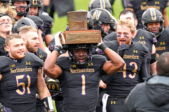 Northwestern running back Jesse Brown (1) celebrates with teammates as he holds the Land of Lincoln Trophy in Evanston, Ill., Saturday.