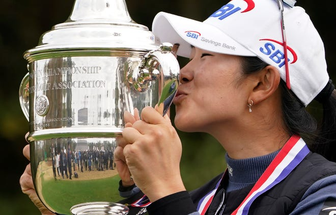 A Lim Kim, of South Korea, kisses the championship trophy after winning the U.S. Women's Open golf tournament, Monday, Dec. 14, 2020, in Houston. (AP Photo/Eric Gay)