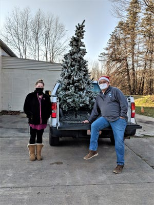 Terry Robinson (right) from the Springfield Township Parks Department helped put the Christmas tree in the back of Elizabeth Hicks' truck.