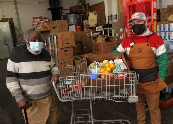Alfred Barfield and Chris Creel, manager at Piggly Wiggly, look over a 23-item box of holiday food donations to be distributed throughout the New Bern community. Barfield has been a local leader in the annual food donation effort for 39 years. There are 160 boxes being distributed with the grocery help of manger Chris Creel and the Piggly Wiggly of New Bern. [Gray Whitley / Sun Journal Staff]