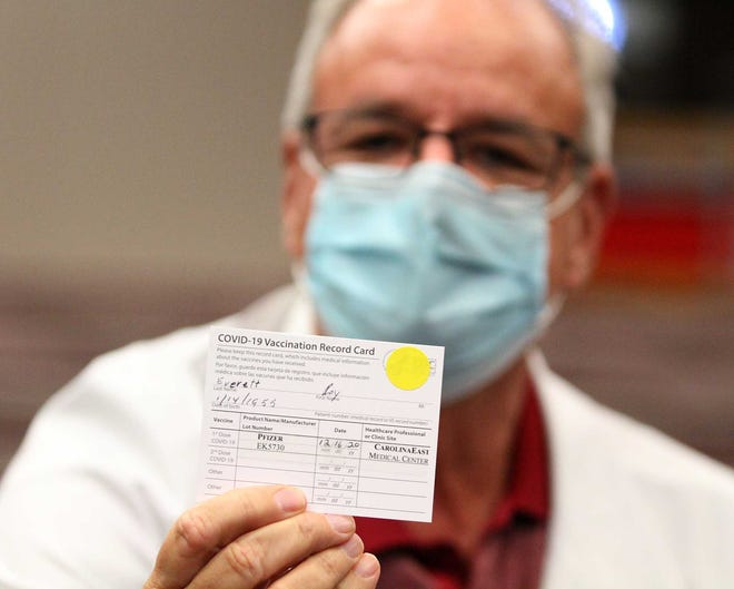 The first COVID-19 vaccinations take place in Craven County for a group of medical staff at CarolinaEast Medical Center in New Bern, NC, Dec. 16, 2020. Roy Everett, MD, shows his vaccination card after being the first Craven County recipient of the COVID-19 vaccine. The vaccine arrives almost a year after COVID-19 began a global pandemic. [Gray Whitley / Sun Journal Staff]