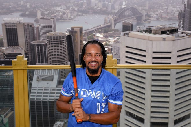 Major League Baseball all-star Manny Ramirez poses for a photograph overlooking Sydney. Ramirez, who was the World Series MVP when the Red Sox broke their 86-year title drought in 2004, is scheduled to begin the season on Thursday for the Sydney Blue Sox in the Australian Baseball League. [Dan Himbrechts/AAP Image via AP]