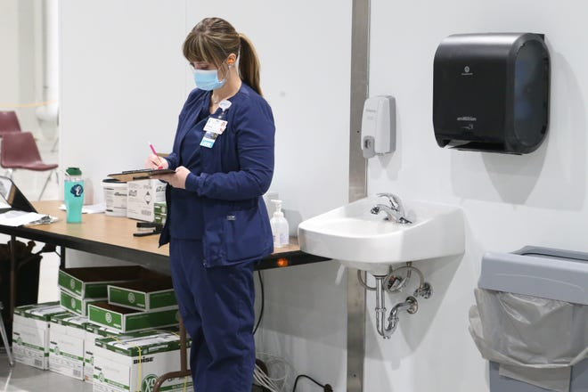 Stormont Vail Health staff work in the make-shift vaccine facilities set up at Stormont Vail Events Center's Exhibition Hall on Wednesday morning to start administering the Pfizer COVID-19 vaccine.