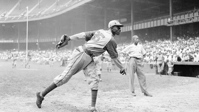 Kansas City Monarch pitcher Satchel Paige warms up at Yankee Stadium before a game against the New York Cuban Stars in 1942.