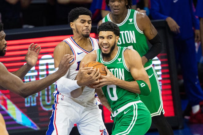 Celtics forward Jayson Tatum (0) drives while being defended by 76ers forward Tobias Harris during the first quarter Tuesday night of Boston's 108-99 preseason loss in Philadelphia.