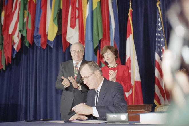 Pres. George H. W. Bush, center, signs the North American Free Trade Agreement during a ceremony at the Organization of American States headquarters, Dec. 17, 1992, Washington, D.C. Canadian Amb. Derek Burney and U.S. Trade Representative Carla Hills applaud during the signing.