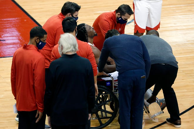 Houston Rockets guard Chris Clemons (middle) reacts as he is wheeled off the court after an injury during the second half against the San Antonio Spurs on Tuesday.