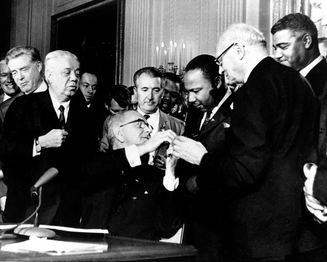 President Lyndon B. Johnson reaches to shake hands with Dr. Martin Luther King Jr. after presenting the civil rights leader with one of the 72 pens used to sign the Civil Rights Act of 1964 in Washington.