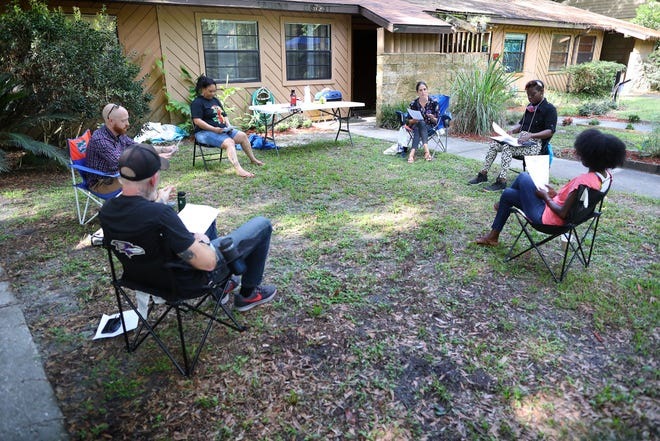 Fellows and leaders with the non-profit Community Spring, which has a mission to dismantle structural poverty and spur economic mobility in the Gainesville area, talk during a meeting socially distant meeting at one of the fellows homes in July.