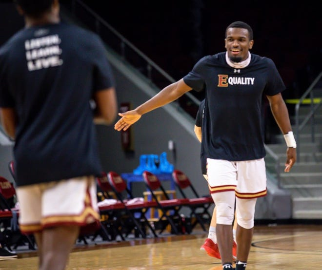 Elon forward Chuck Hannah, right, greets teammates during warm-ups prior to the Phoenix's victory against High Point last month.